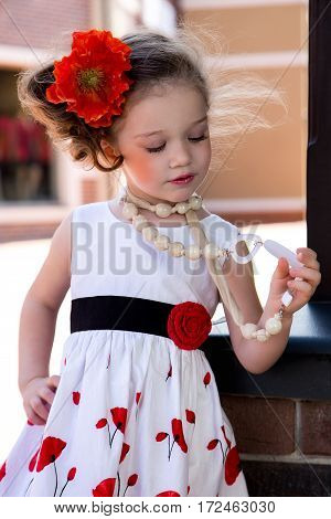 Little girl in a dress with beads and a flower in her hair