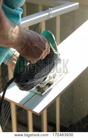 Carpenter working with electric jigsaw or fretsaw