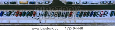 Long line of parked cars near the house. The top view on parked cars. Neatly parked cars in winter