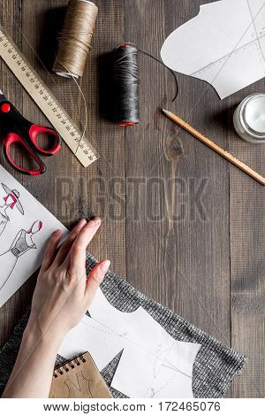 desktop designer clothes with tools top view at wooden table.
