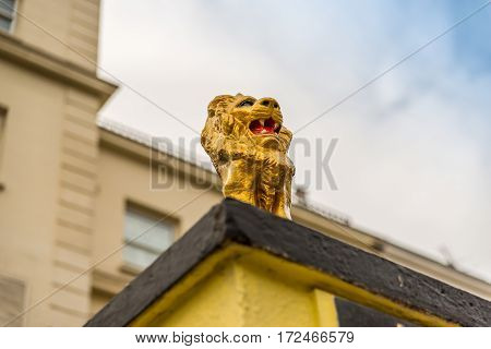side view on a gold lion on a pedestal in front of the gate to the estate gold hand-painted sculpture a fantastic decoration in front of the building