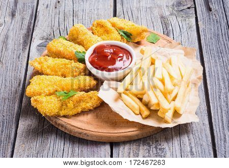 chicken strips and French fries on rustic wooden background