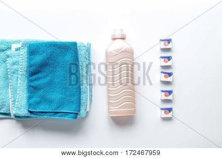 Pile of colorful clean towels with detergent on white background top view