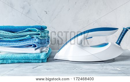 Launry washing set with blue towels and iron on gray desk background mock up