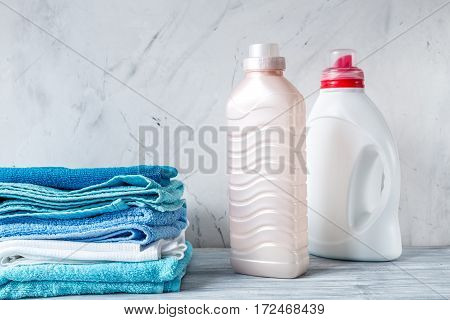 laundry set with bright towels and plastic bottels of detergent on gray table background mock up