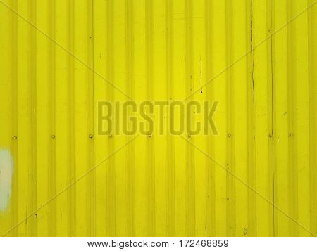 Bright yellow tin wall background texture with screws in the lower part.
