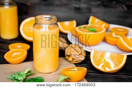 healthy morning with fresh orange and mint juice in bottle on kitchen background