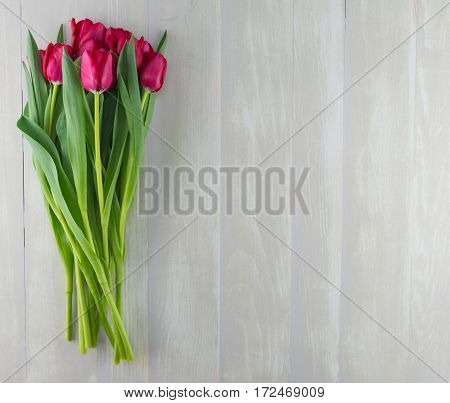 Red Tulips on Weathered Gray Table Top with copy space to right