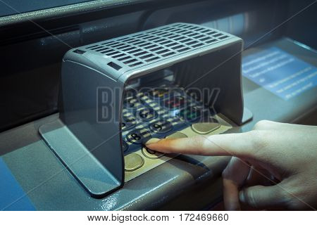 finger point at A.T.M. numpad keypad with guard for protect and use deposit or withdraw money closeup
