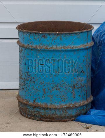 Rusty Blue Bin sitting on sidewalk in industrial district