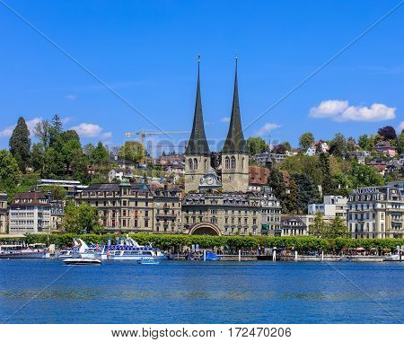 Lucerne, Switzerland - 8 May, 2016: people in boats on Lake Lucerne, towers of the Church of St. Leodegar and buildings of the city in the background. Lucerne is a city in central Switzerland, it is the capital of the Swiss canton of Lucerne.