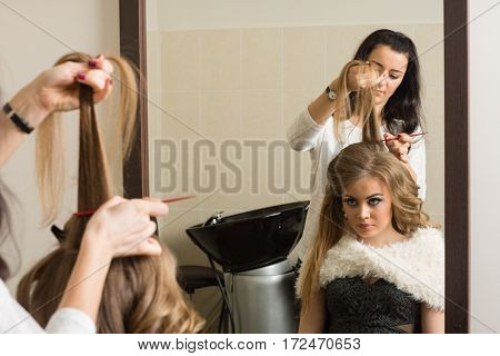 Female hairdresser makes hair styling girl in a beauty salon.