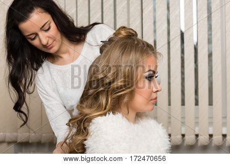Female hair stylist girl makes hair styling in a beauty salon.