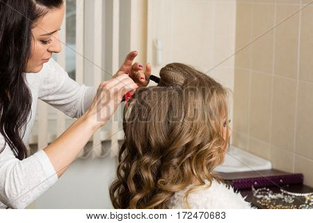 Hairdresser makes hair styling girl in a beauty salon.