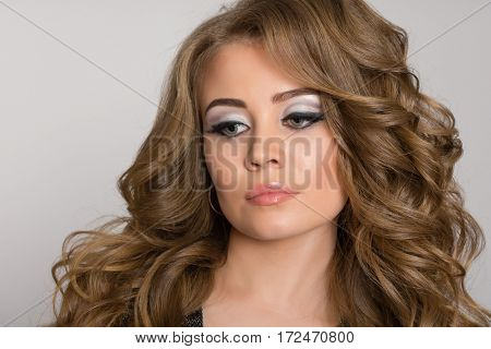 Beautiful blonde with make-up with curly hair on a gray background.
