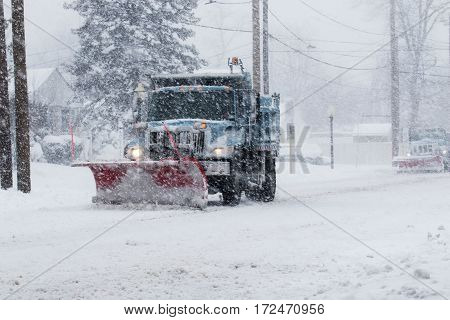 Snow plow doing its job during a blizzard