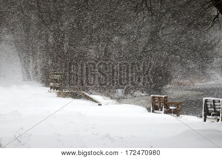 Snow blowing over a lake with park benches and a wooden bridge in view
