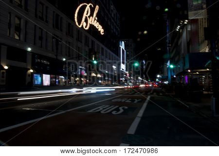 New york city street view at night as cars pass by and the words Believe light up on a building