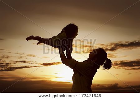 Happy woman playing with little girl on the beach at sunset. Mother Day Concept.