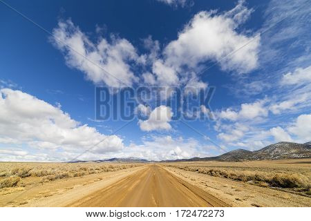 Dirt Road In The Nevada Desert Under Blue Sky With Clouds.  Road Is Wet Dirt And Mud.