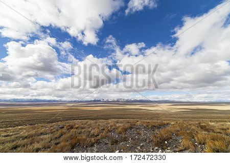Wide Open Empty Desert Landscape In Nevada During Winter With Blue Skies And Clouds.  Mountains In T