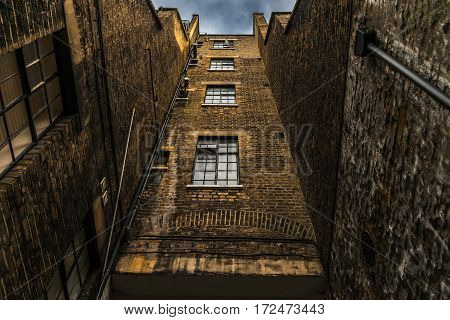 up view of the old tall brick building with characteristic large windows gutters and vents English architecture