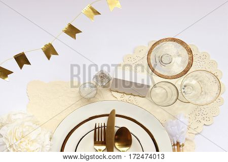 Chic and elegant formal table setting with gold party decorations.
