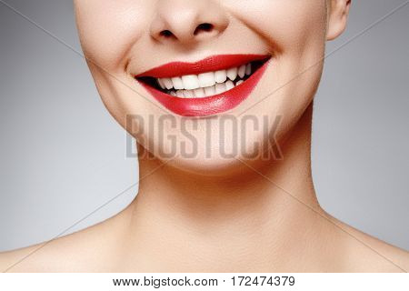 Wide smile of young beautiful woman with perfect healthy white teeth on grey background. Dental whitening ortodont care tooth and wellness. Red lipstick makeup on female lips.