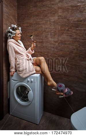 Young attractive housewife in the bathroom. Girl in a bathrobe and curlers doing morning makeup. Makeup Brush. Good morning.