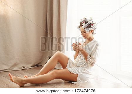 Young attractive housewife sitting on the floor near the window. Girl in a bathrobe and curlers drinking morning coffee. Good morning. She holds a mug of hot drink