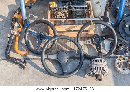 Old automobile machine parts steering wheels and used machine parts place on street walk in second hand market for selling.