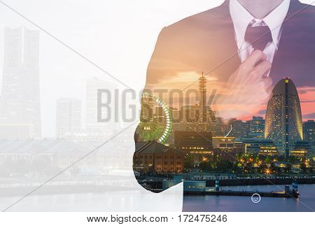 Double Exposure Of Businessman In Suit Tying Necktie Against The City