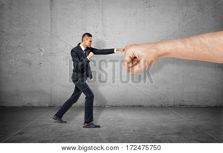 Businessman is trying to resist a huge male fist and move it away on the gray background. Market pressure. Being competitive. Small business protection