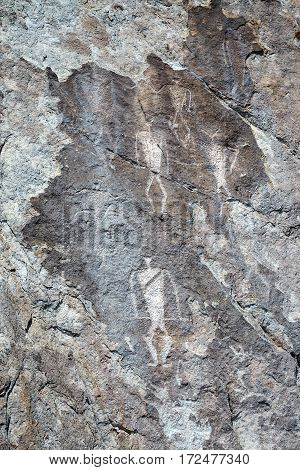 Ancient petroglyphs of dancing shamans with horns, rock paintings of ancient buryat tribe, lake Baikal coast