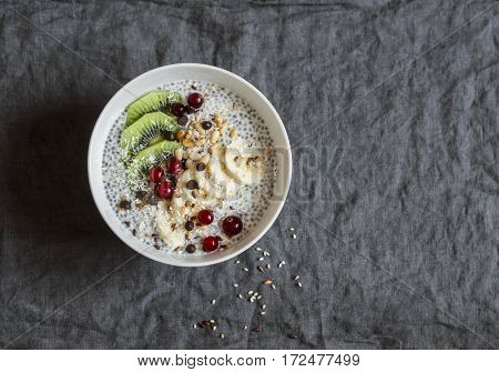 Chia pudding with fruits seeds and nuts on a dark background top view. Healthy breakfast or snack
