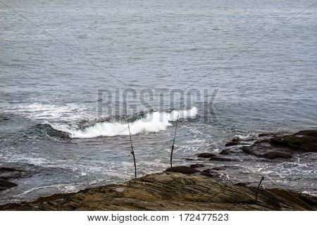 Lonely fishing poles set on a rock.