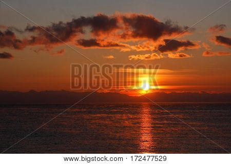 Sunset in red colors with sunlight path on water surface in winter