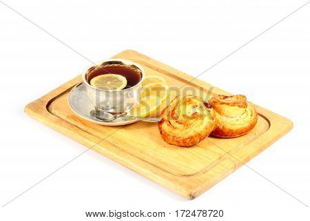 beautiful morning spiral-shaped bun and a porcelain cup of hot tea with a slice of lemon on a wooden tray