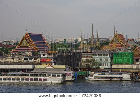 Bangkok, Thailand - July 25, 2010: View from Wat Arun temple to Chao Phraya river boats and old town buildings on bank.