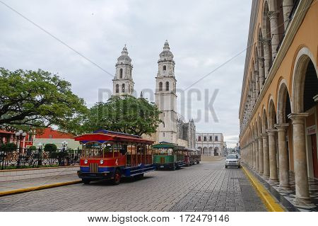 Campeche, Mexico - February 01, 2010: Independence Plaza tourist trains and cathedral on the opposite side of the square.