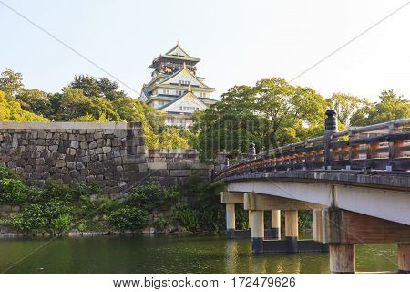Osaka Castle with wooden Gokurakubashi Bridge in front of the castle during summer season this castle is very famous tourist attraction of Osaka Japan.