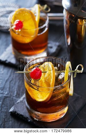 old fashioned cocktails on cool slate garnished with orange slice, lemon peel, and cherry