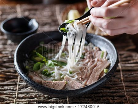 eating bowl of beef brisket pho with chopsticks and spoon