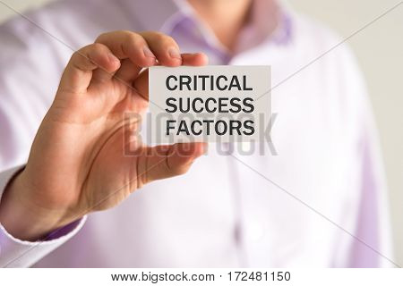 Businessman Holding A Card With Text Critical Success Factors