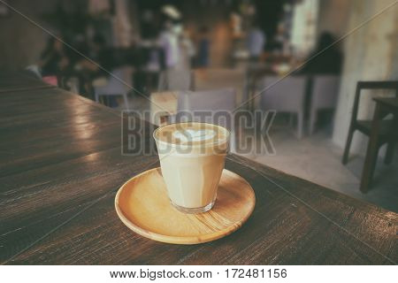A cup of piccolo latte with wooden saucer in cafeteria - vintage style effect