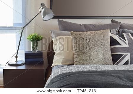 Modern Bedroom With Gray Pillow And Lamp On Wooden Bedside Table At Home