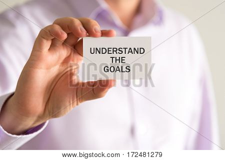 Businessman Holding A Card With Text Understand The Goals