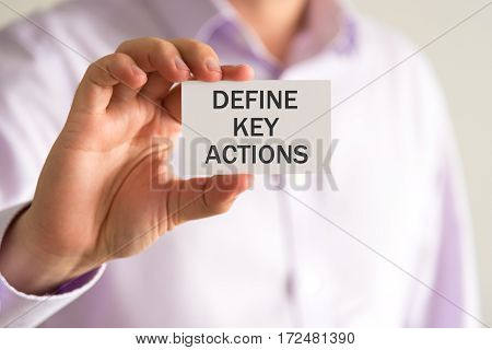 Businessman Holding A Card With Text Define Key Actions