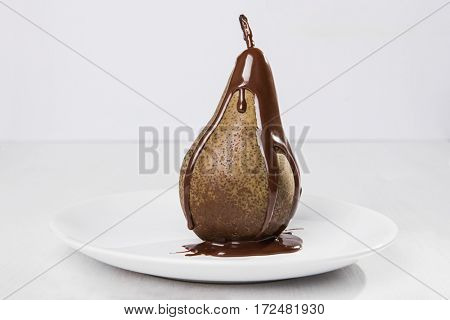Juicy pear drenched in chocolate