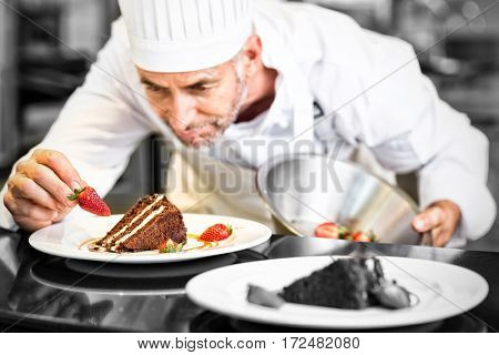 Closeup of a concentrated male pastry chef decorating desserts in the kitchen